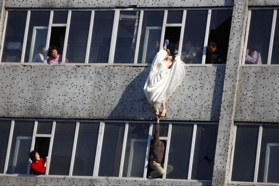 Government workers on the 6th and 7th floor work together to lift a girl who had jumped out a window back to safety.