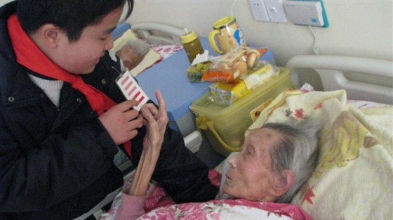 Hang Yibo, Chinese Young Pioneer, visiting an elderly woman in a hospital.
