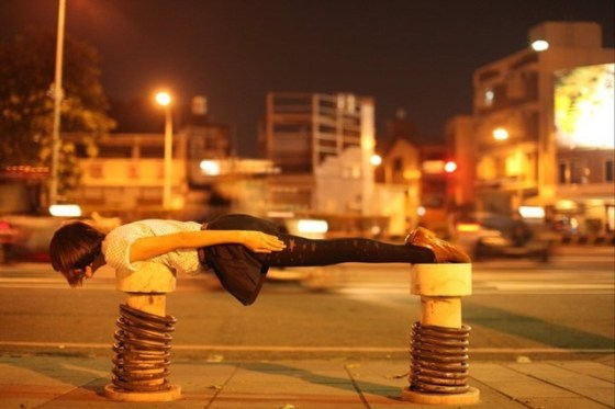 A Taiwanese girl lies face down flat across two poles in Taiwan.