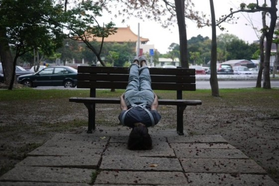 A girl in Taiwan lies head down off a park bench.