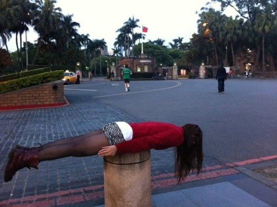 A Taiwanese girl lies stiff and straight face down on a pillar.