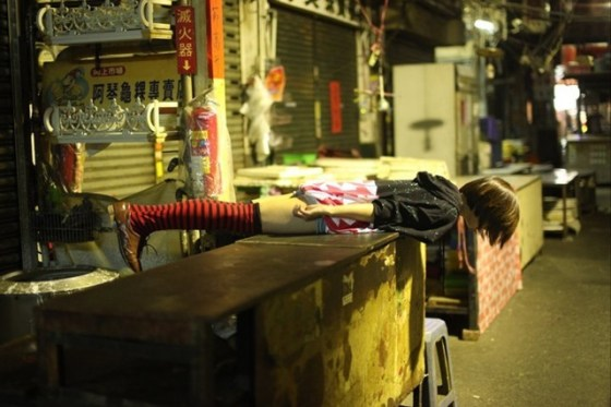 Taiwanese girl lies face down and straight over a counter in a food market.