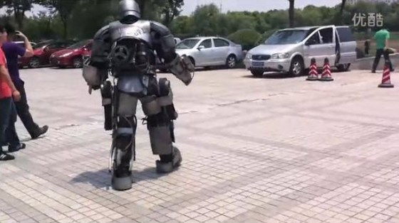 A Chinese man walking around in a self-made Iron Man MK I Armor suit.