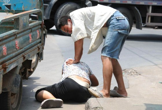 A Chinese husband presses his wife down onto the ground in public during a physical fight.