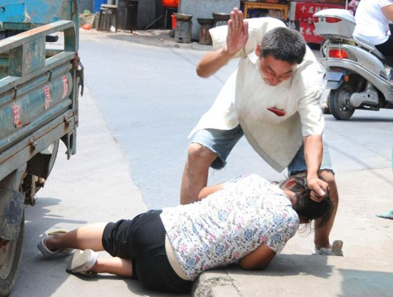 A Chinese migrant worker smacks his wife in public while holding her by her hair.