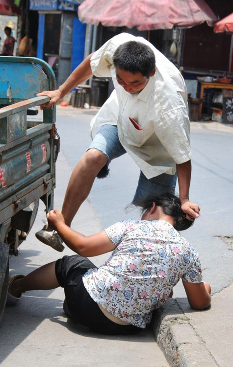 An angry Chinese husband kicking and pulling his wife's hair on a public street in Zhejiang province of China.