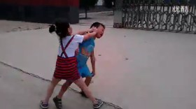 The little girl, shoving the little boy's head.