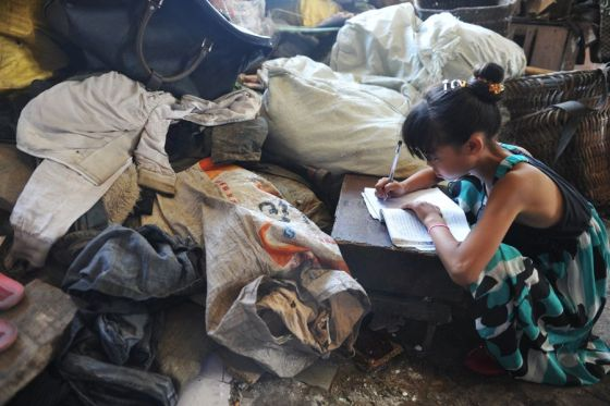A small Chinese girl doing her homework beside a pile of garbage bags in Guiyang.