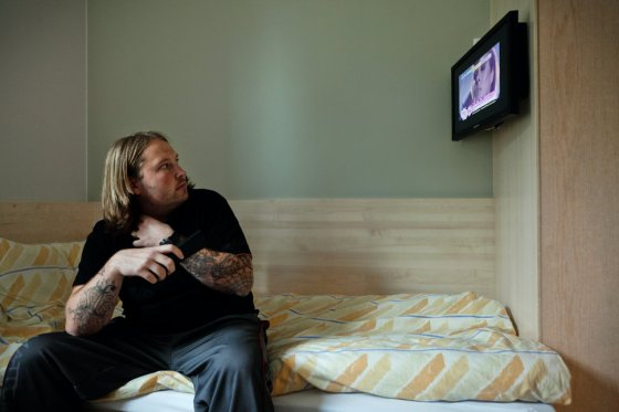 An inmate is watching television while sitting on his bed inside one of the private prison cells built with en-suite bathroom and various other amenities in the luxurious Halden Fengsel, (prison) near Oslo.