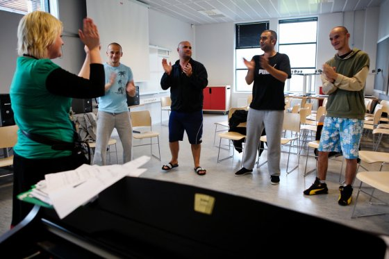 Inmates (facing camera) and their instructor are clapping hands and singing during the time they regularly spend learning and practicing music arts inside the luxurious Halden Fengsel, (prison) near Oslo.