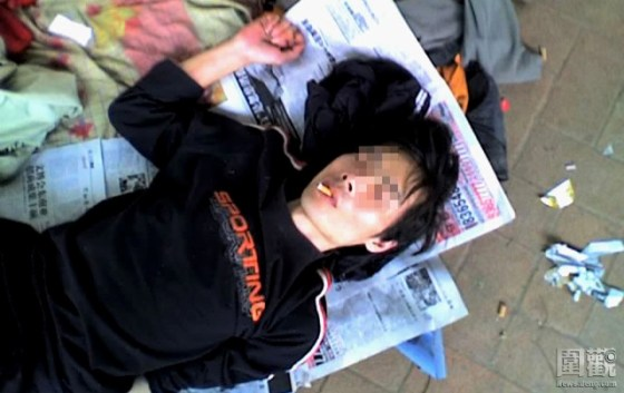 A Chinese woman lies on the ground high on drugs.