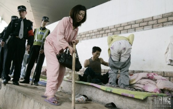 A Chinese woman and drug addict hunched over leaning on a walking stick as Shenzhen police drive them out from their home under the overpass.
