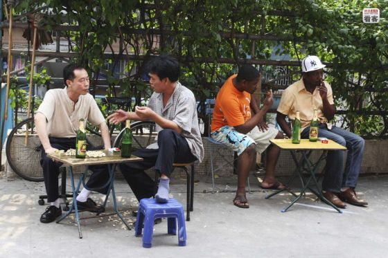 Africans and Chinese eating on the street.