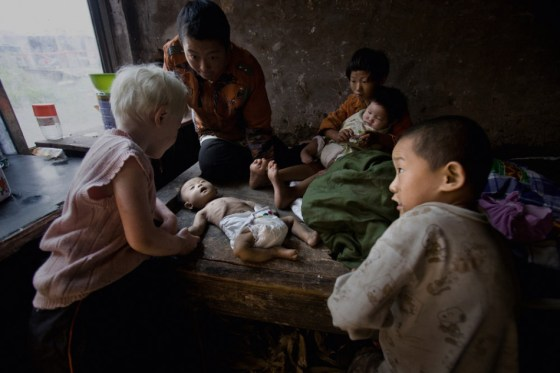 Several children adopted by Yuan Lihai surround an abandoned baby who has just passed away from illness.