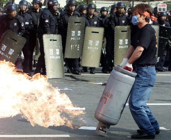 A Korean protester spewing flames from a propane gas tank with riot police in the background.
