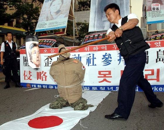 "A Korean nationalist ""beheads"" a Japanese government official during a protest in front of the Japanese Embassy in Seoul, Korea."