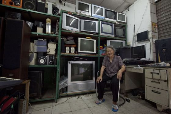 Yang Wu's mother cries in his electronic appliances repair shop.