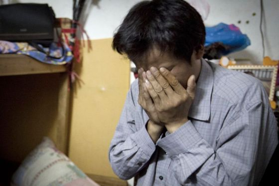 Yang Wu covers his face in tears.