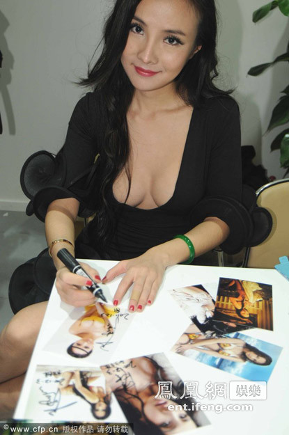 Gan Lulu wearing a revealing low-cut black dress signing autographs for fans.