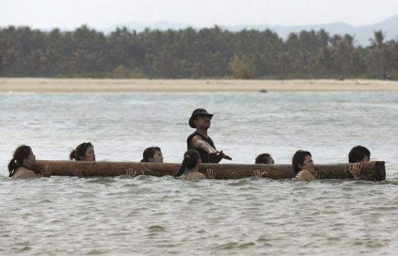 A row of Chinese female bodyguards carrying a log in the water during training on a beach.