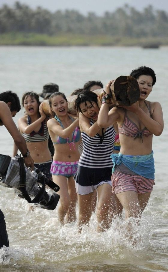 A row of Chinese female bodyguards carrying a log during training on a beach.