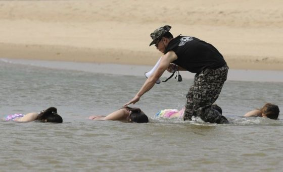 Chinese female bodyguard trainees holding their breath under water.
