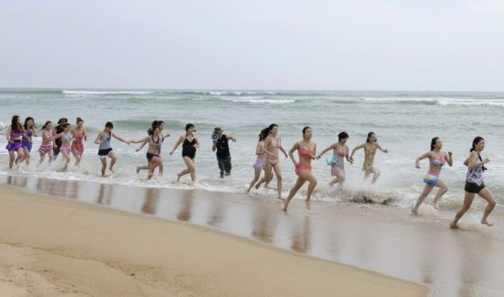 Chinese female bodyguards in training running cross country on a Hainan beach in China.