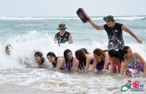 Chinese female bodyguards training in swimsuits on a beach in Hainan, China.