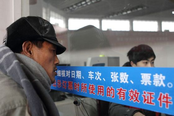 A Chinese migrant worker in front of a train ticketing window to purchase tickets home for the Spring Festival holiday.