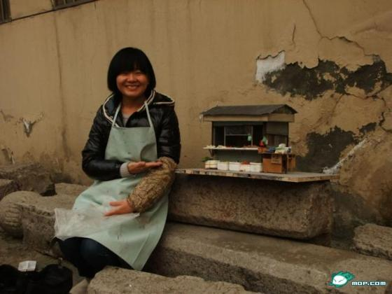 A graduating student from China's Xi'an Academy of Fine Arts proudly shows off her scale-model vegetable stand.