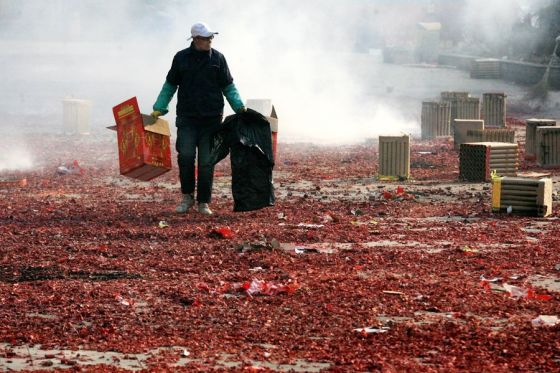 A Chinese sanitation worker walking amongst a sea of red firecracker litter that covers the streets of China during Chinese New Year.