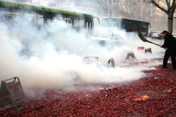 A Chinese man with a broom tries to smother smoldering firecracker shells.