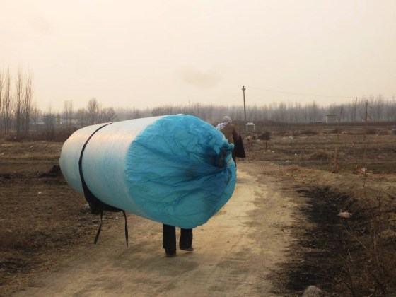 A Chinese villager carrying home a long plastic bag inflated with natural gas illegally siphoned off from a nearby oil well.