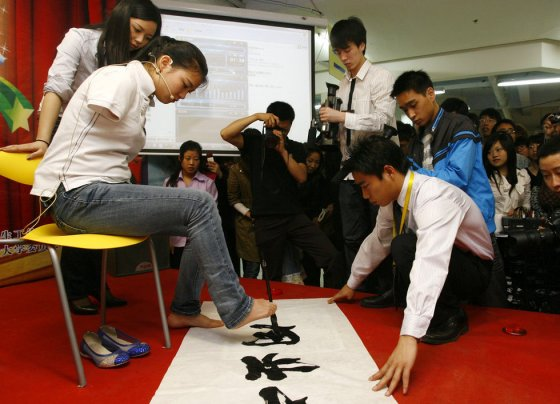 An Chinese girl without arms uses her foot to write Chinese calligraphy in front of university students..
