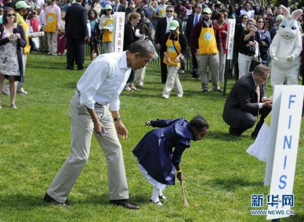 Obama is playing Easter Egg Roll together with little children.