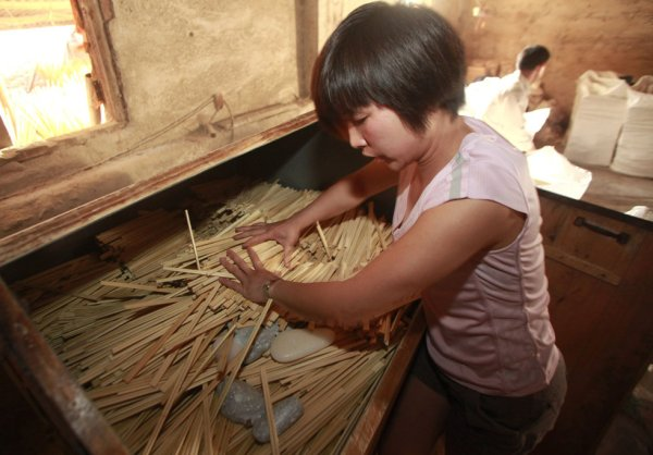 A young girl at a disposable chopsticks manufacturing plant in Guangxi province, China.