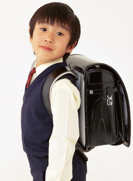 Asian boy with big black backpack.