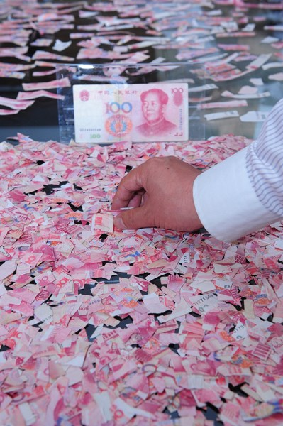 Thousands of pieces of 100 RMB cash notes torn into pieces with bank workers trying to piece them back together.