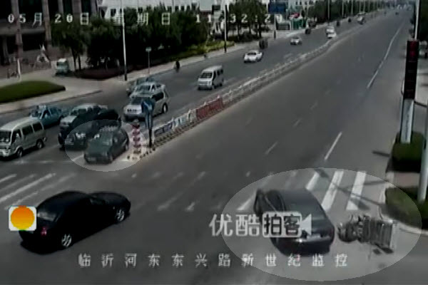 In Linyi, China, an old man falls off his electric three-wheeled motorcycle to avoid hitting a black Audi.