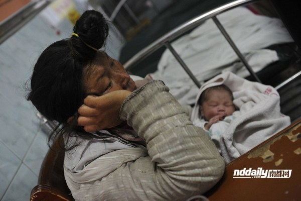 Mentally ill Chinese homeless woman holding her baby in a Guangzhou hospital.