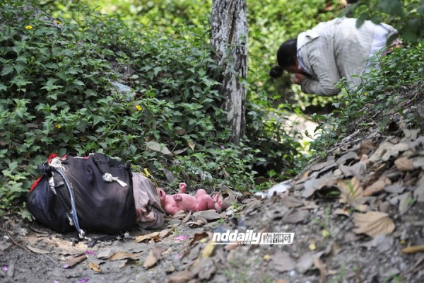 The mentally ill homeless Chinese woman's baby lies naked on the ground as she drinks water from a roadside drainage ditch.