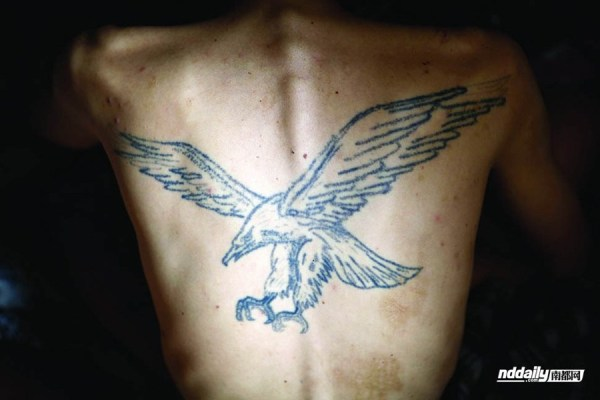 Wu Guilin, a drug addict in Guangdong province of China, with an eagle tattooed on his back.