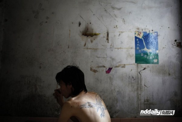 Chinese drug addict Wu Guilin inside a filthy and run down room that is his home.