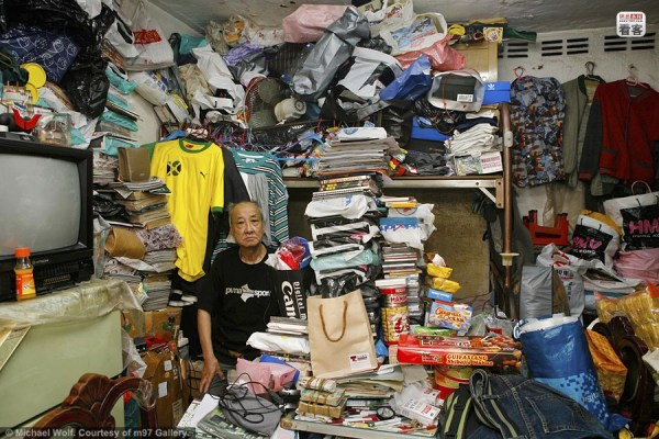 Former Hong Kong Shek Kip Mei residents and the 100 square foot room they lived in, photographed by Michael Wolf.