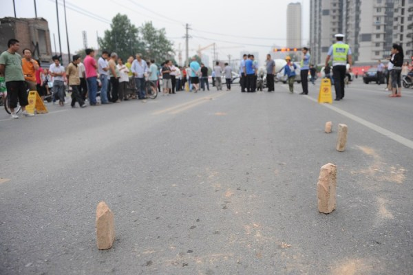Bricks placed on the road surrounding the scene of a tragic traffic accident that claimed the life an 11-year-old Chinese schoolgirl in Xi'an, China.