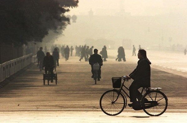 A Chinese person riding on a bike against the hazy smoggy polluted Beijing air background.