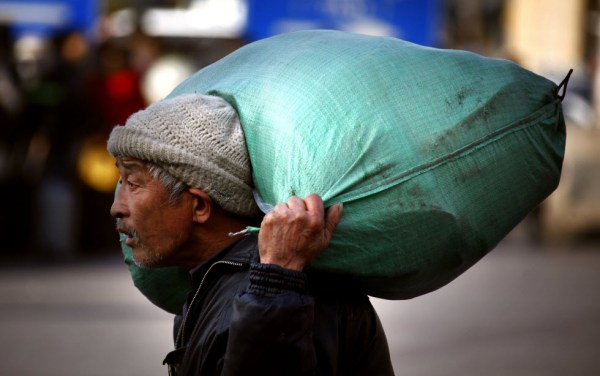 An elderly Chinese migrant worker carrying a bag on his back and shoulders.