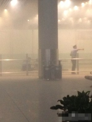 Smoke from the explosion at Beijing Airport T3 terminal as airport personnel and security respond to the incident.