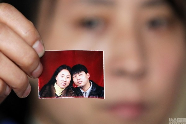 Zhang Jing holding up a photo of herself with Xia Junfeng, the Chinese street vendor who was given the death penalty for killing two chengguan officers in a fight.