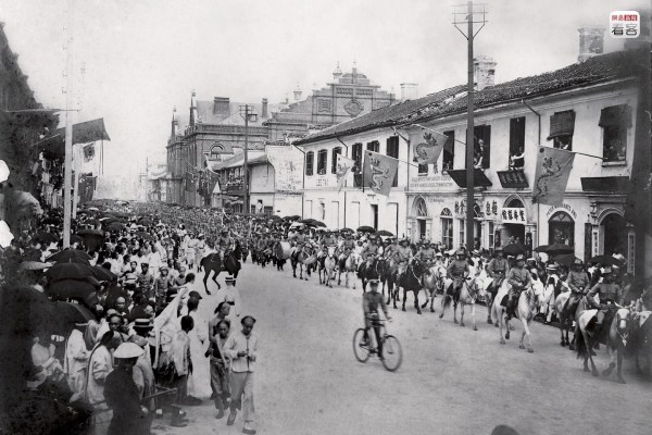 """The development of """"Modern Shanghai"""" started at the beginning of the 20th century. Municipal government and public facilities brought by international settlements; telegrams, telephones, and movies, balls, and other Western lifestyles brought by technological development; these factors collectively created a unique city: Shanghai. Photo is of 1902, of the Shanghai Volunteer Corps proceeding along Nanjing Road, participating in a parade. The Shanghai Volunteer Corps were established in 1853, with the purpose of protecting foreigners against the chaos of war. (Photo source: Shanghai: 1842-2010, Portrait of a Great City Post Wave Publishing)"""